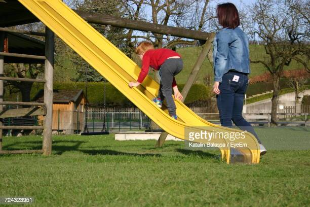 Side View Of Mother Looking At Son Climbing Slide At Playground