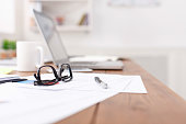 Close up of wooden desktop with glasses, laptop, coffee cup and other items on office space background, selective focus