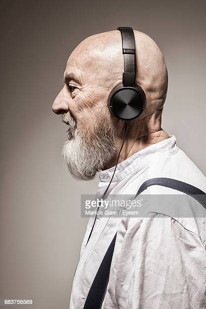 Side View Of Old Man Wearing Headphones Against Gray Background