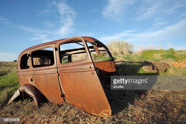 side view of one rusty car wreck against blue sky