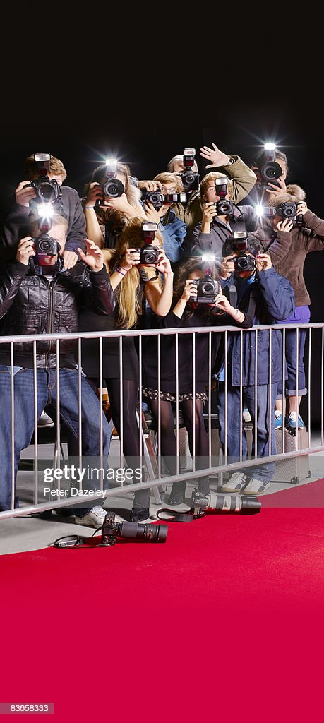 Side view of paparazzi behind railings