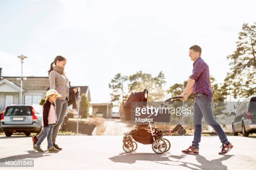 Side view of parents with baby carriage and daughter walking on street