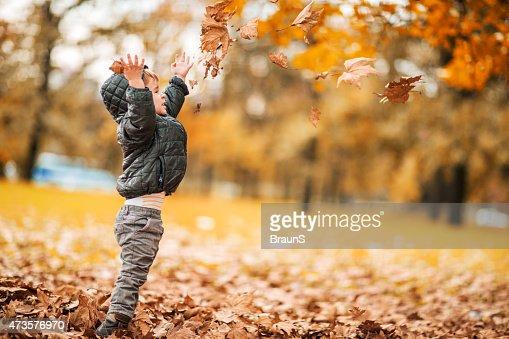 Vista lateral de divertido niño pequeño tirando Hojas otoñales al aire libre.