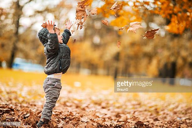 Side view of playful little boy throwing autumn leaves outdoors.