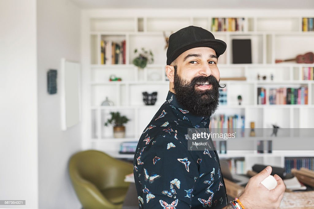 Side view of portrait of happy male architect standing in home office
