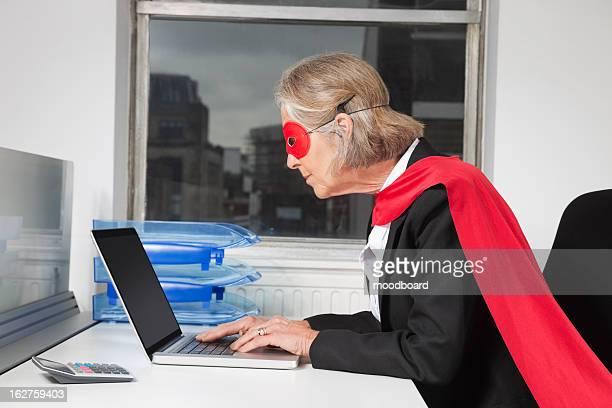 Side view of senior businesswoman in superhero costume using laptop at office desk