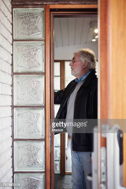 Side view of senior man standing in room seen through ajar