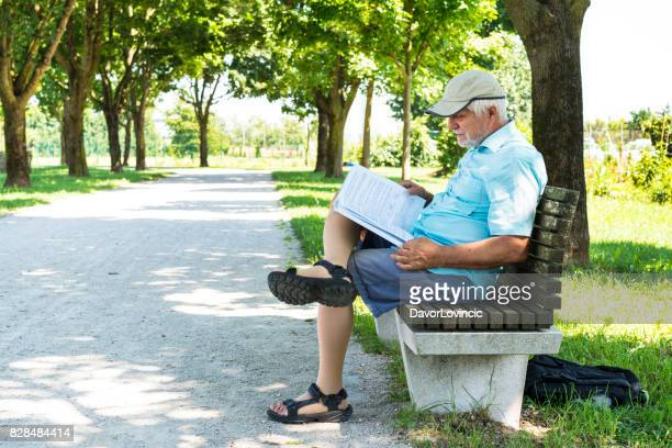 Side view of Senior reading a book while sitting on bench in shadow on The Trail of Remembrance and Comradeship in Ljubljana, Slovenia