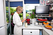Side view of senior woman filling ground espresso in holder at kitchen