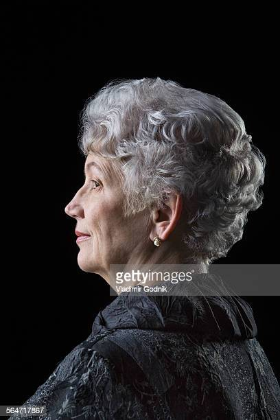 Side view of senior woman over black background