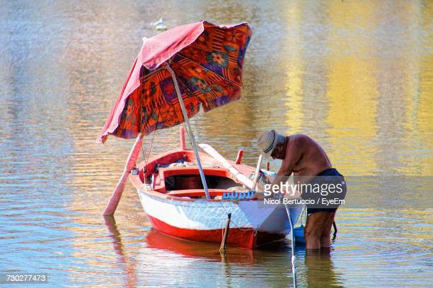 Side View Of Shirtless Senior Man With Boat In Lake