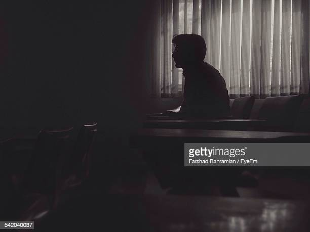 Side View Of Silhouette Man Sitting On Chair In Darkroom
