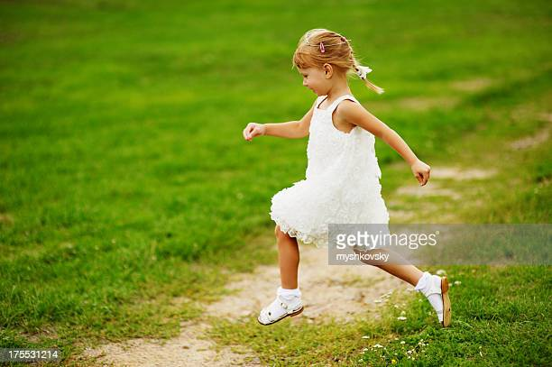 Side view of smiling girl in white dress running in the park