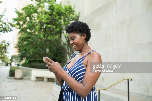 Side view of smiling woman text messaging through mobile phone against buildings in city