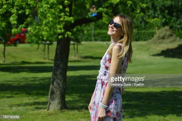 Side View Of Smiling Young Woman Standing On Grassy Field During Sunny Day