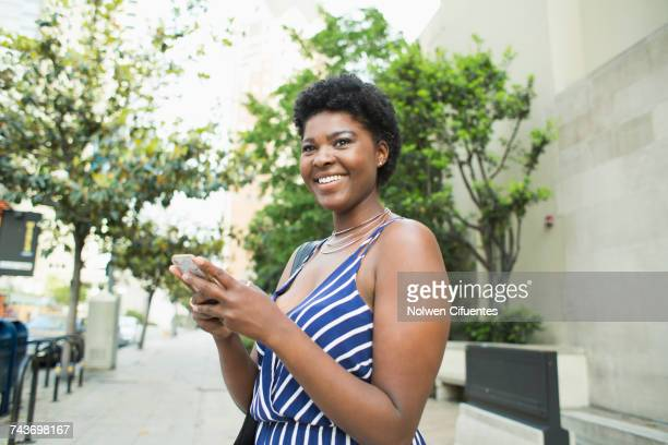 Side view of smiling young woman using mobile phone in city