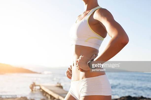 Side view of sportswoman standing at beach