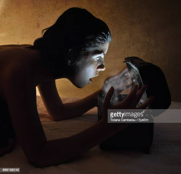 Side View Of Surprised Woman Looking In Illuminated Box On Bed Against Wall