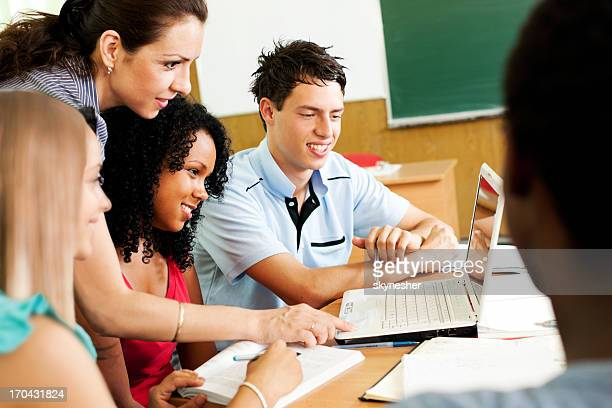 Side view of teacher helping students use computer.