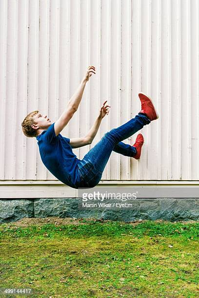 Side view of teenage boy lying mid air over grass