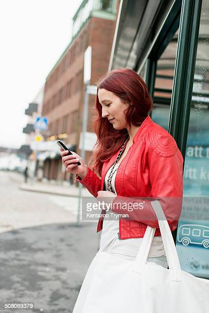 Side view of teenage girl reading text message on city street