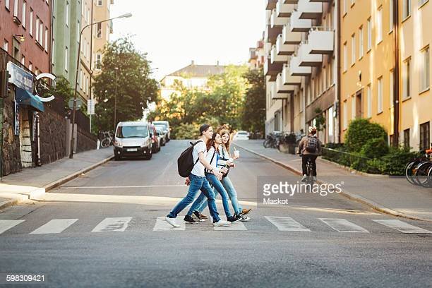 Side view of teenagers crossing road in city