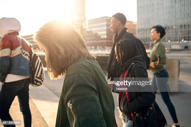 Side view of teenagers walking on street against buildings in city
