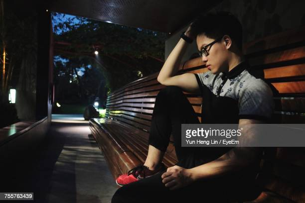 Side View Of Thoughtful Man Sitting On Bench At Night