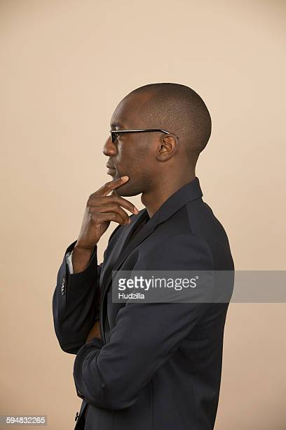 Side view of thoughtful man standing against colored background