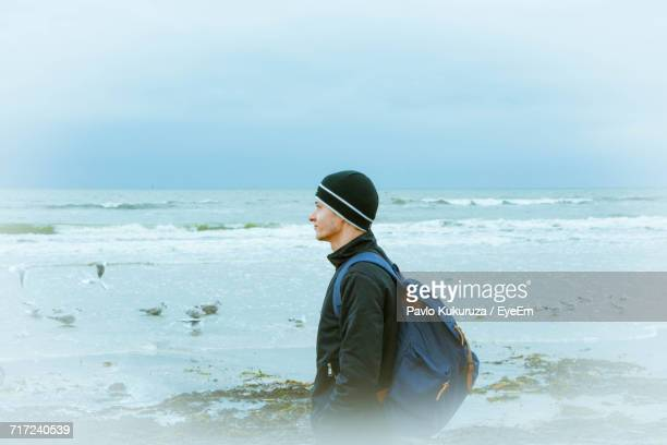 Side View Of Thoughtful Man With Backpack Standing On Sea Shore At Beach