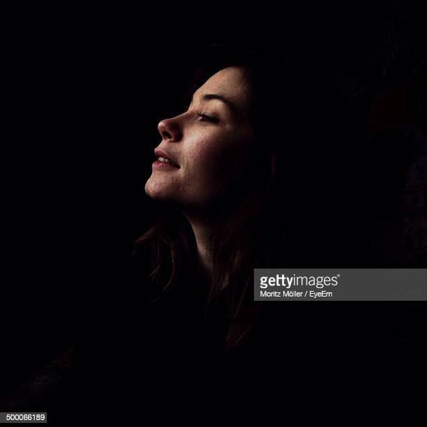 Side view of thoughtful young woman over black background