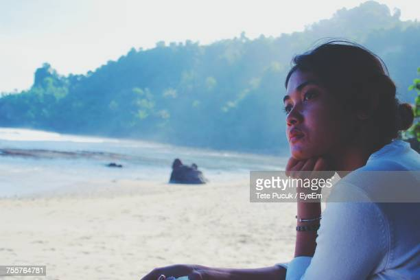 Side View Of Thoughtful Young Woman Sitting At Beach