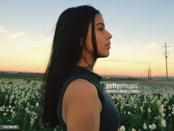 Side View Of Thoughtful Young Woman Standing On Field Against Sky During Sunset