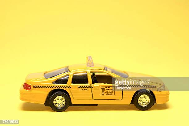 Side view of toy yellow cab with a yellow background