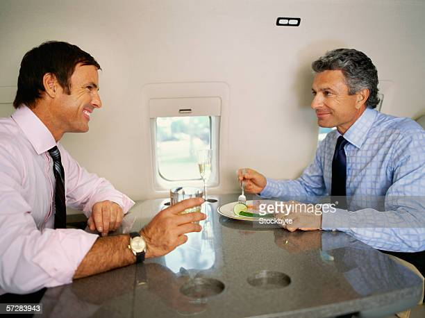Side view of two businessmen having a business lunch in an airplane