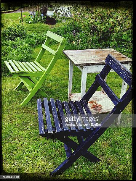 Side view of two empty chairs with side table on grass