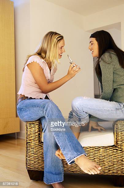 Side view of two teenage girls holding mobile phones
