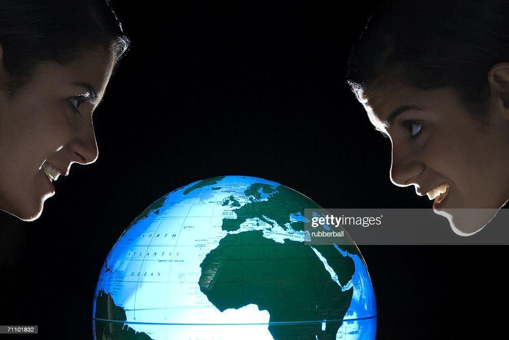 Side view of two teenage girls near a glowing globe : Stock Photo