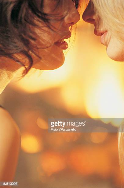 Side VIew of Two Women With Their Mouths Close to Each Other