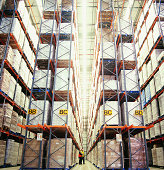 Side View of Two Workers Standing in Aisle in Warehouse