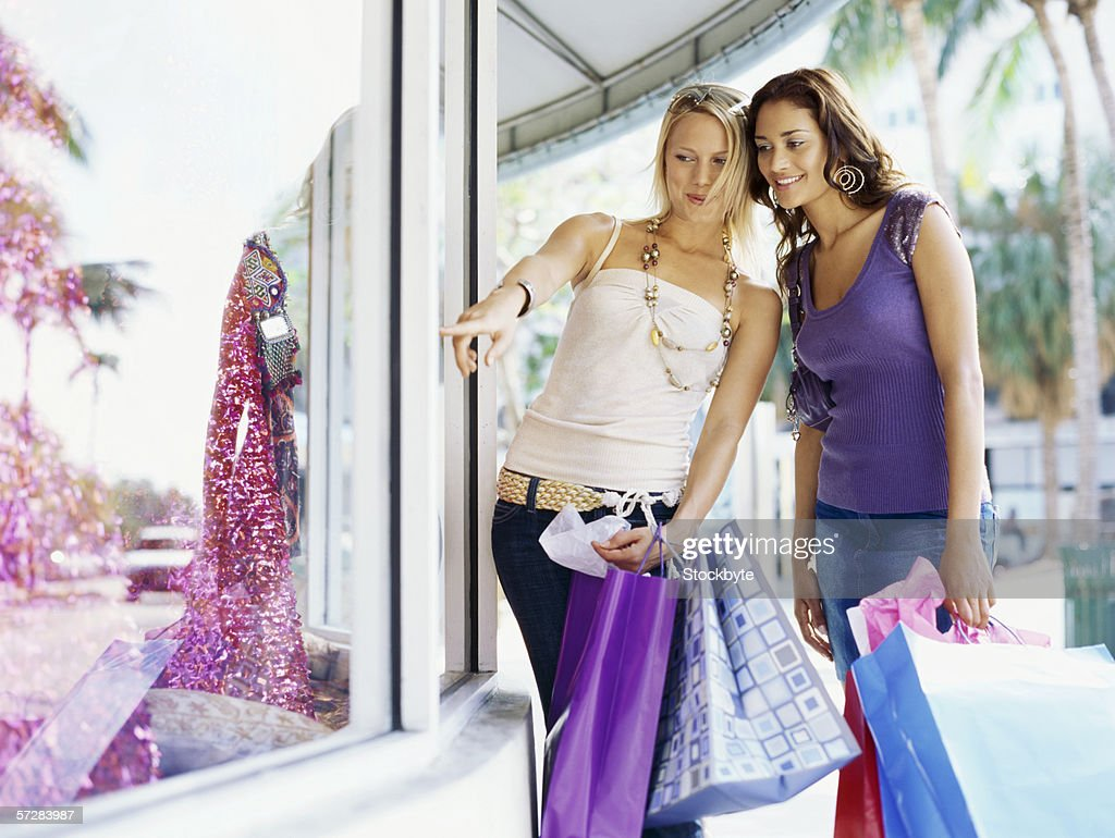 Side view of two young women standing in front of a shop window : Stock Photo