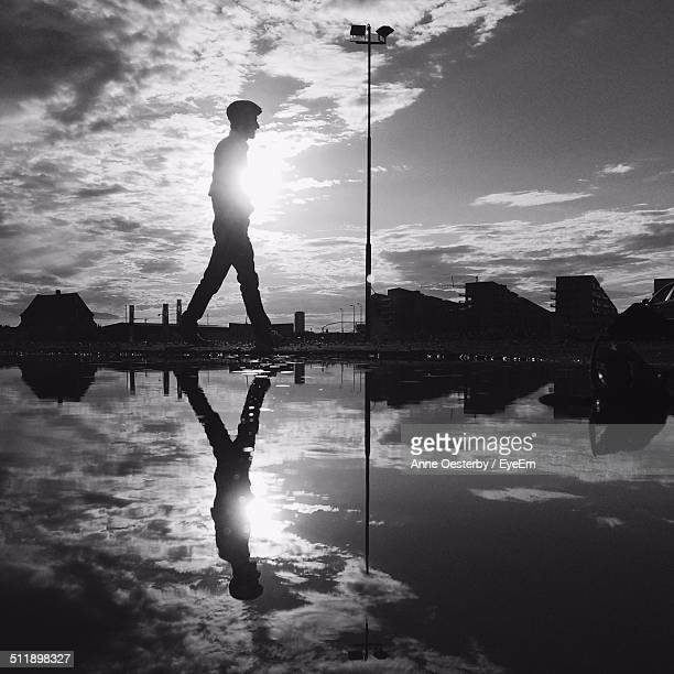 Side view of walking man reflected in puddle