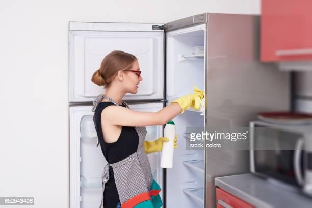 Seitenansicht der Frau den Kühlschrank reinigen