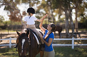 Side view of woman giving high five to girl sitting on horse in paddock