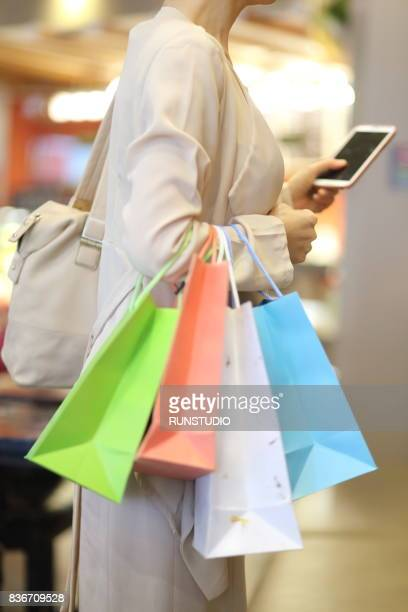 side view of woman holding shopping bags