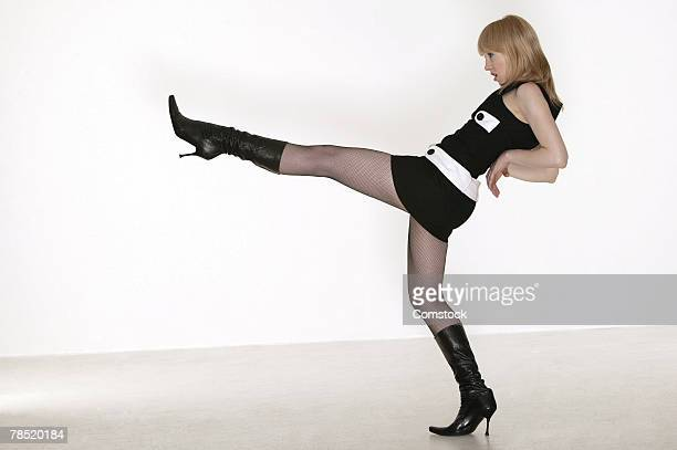 Side view of woman in stiletto boots kicking