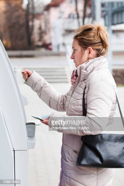 Side View Of Woman Inserting Debit Card In Atm Machine