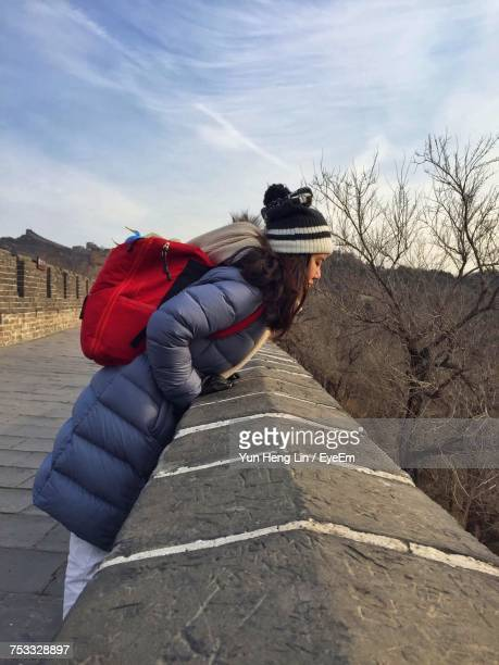Side View Of Woman Leaning On Fortified Wall Against Sky
