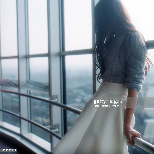 Side View Of Woman Leaning On Railing By Window