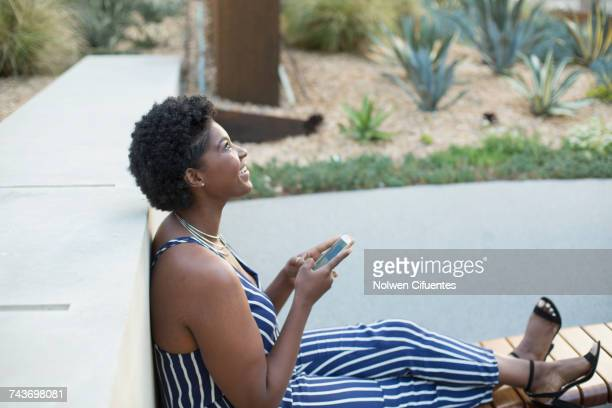 Side view of woman leaning on retaining wall sitting with mobile phone while looking up at park